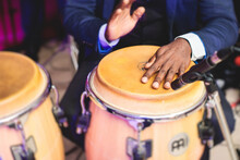 Bongo Drummer Percussionist Performing On A Stage With Conga Drums Set Kit During Jazz Rock Show Performance, With Latin Cuban Band Performing In The Background, Drummer Point Of View