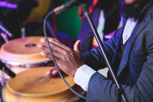 Fototapeta Bongo drummer percussionist performing on a stage with conga drums set kit durin