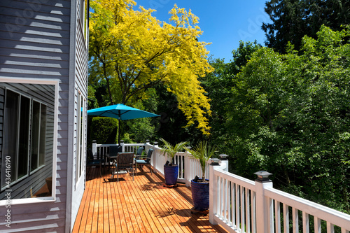 Canvastavla Home outdoor wooden deck with trees in full bloom and clear blue sky plus furnit