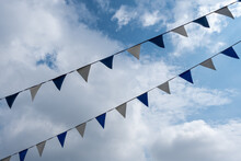 Triangle Flags Hanging In Front Of Cloudy Sky Background