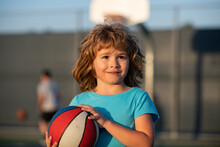 Basketball Game. Kid Training With Basket Ball On Basketball Court Outdoor.