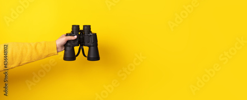 Female hand holds black binoculars on a yellow background. Looking through binoculars, travel, find and search concept. Banner.
