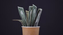 Dollar Bills In A Paper Cup. National Money. Investment And Profit. Cash. American Dollars. Dark Background. Concept.