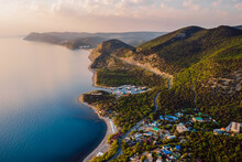 Aerial View Of Coastline With Blue Sea, Mountains With Trees, Cliffs With Sunset Light And Clouds.