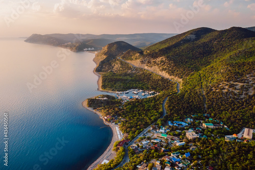 Foto Aerial view of coastline with blue sea, mountains with trees, cliffs with sunset light and clouds