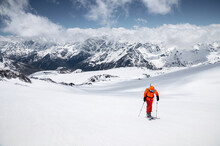 Young Male Freerider Guide In A Yellow Ski Suit With A Backpack On His Shoulders Climbing The Mountain On Skis On A Sunny Day.