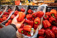 Man Hand Holding Sweet Red Pepper In Grocery Store