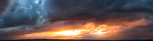 Dramatic Dark Sunset. Panorama Of Dark Rain Clouds In The Evening. A Rich Red Sky Before A Night Thunderstorm