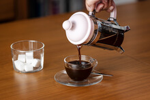 Woman Hand Pouring Coffee With French Press Or Plunger Into Cup On Wooden Table