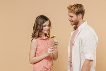 Smiling Excited Young Parent Man With Child Teen Girl In Casual Pastel Clothes Daddy Little Kid Daughter Gifting Giving Gerbera Flower Isolated On Beige Background. Women's Day Love Family Concept