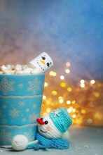 Winter Mug With Marshmellow Snowman And Knitted Handmade Stand Snowman In Scarf Against Background Of Festive Lights