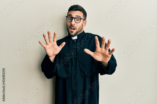 Obraz na płótnie Young hispanic man wearing priest uniform standing over white background afraid and terrified with fear expression stop gesture with hands, shouting in shock