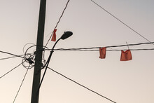 Low Angle View Of Orange Construction Marker Flags On Electrical Wires Coming From Street Light Pole