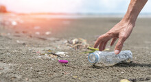 CSR Corporate Sustainable Responsibility Concept. Hand Of Business Man Picking Plastic Bottle Garbage On The Beach To Keep The Sea Environment Clean.