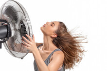 Young Woman Cooling Down With Electric Fan