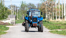 The Tractor Is Driving Along The Road