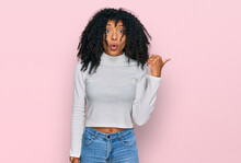 Young African American Girl Wearing Casual Clothes Surprised Pointing With Hand Finger To The Side, Open Mouth Amazed Expression.