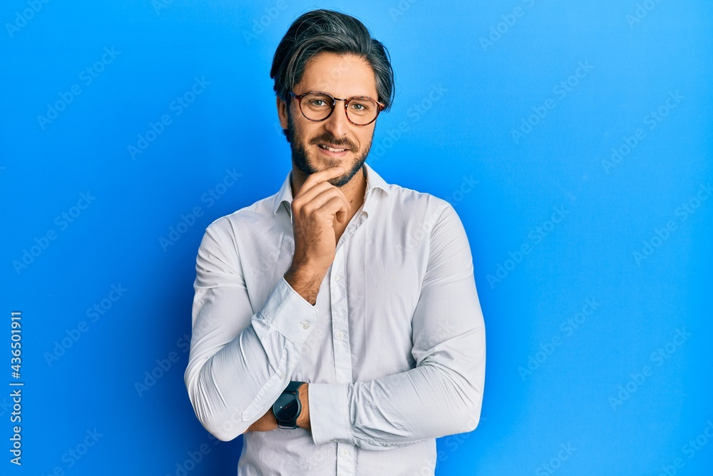 Leinwandbild Motiv - Krakenimages.com : Young hispanic man wearing casual clothes and glasses smiling looking confident at the camera with crossed arms and hand on chin. thinking positive.