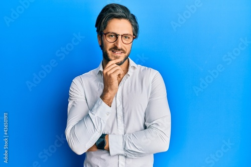 Young hispanic man wearing casual clothes and glasses smiling looking confident at the camera with crossed arms and hand on chin. thinking positive.