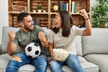 Young Latin Couple Watching Soccer Match Eating Porpcorn At Home.