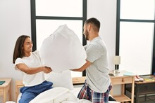 Young Latin Couple Smiling Happy Fighting With Pillows On The Bed At Home.