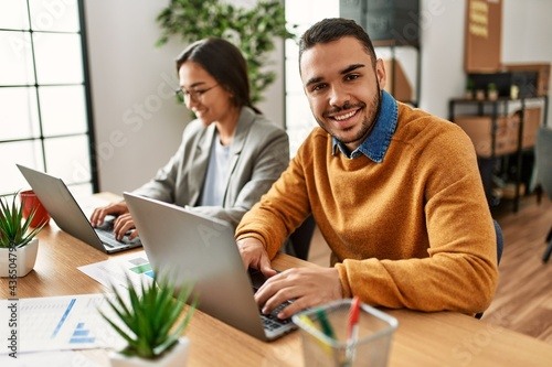 Two business workers smiling happy working sitting on desk at the office.