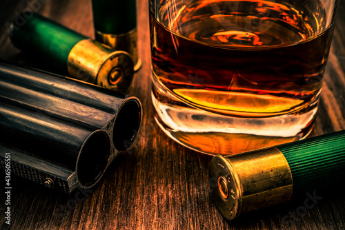 Obraz na plátne Double-barreled shotgun barrel and glass of whiskey with ammo close-up
