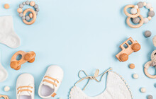 Baby Shoes, Bib And Teether On Pastel Background. Organic Newborn Accessories