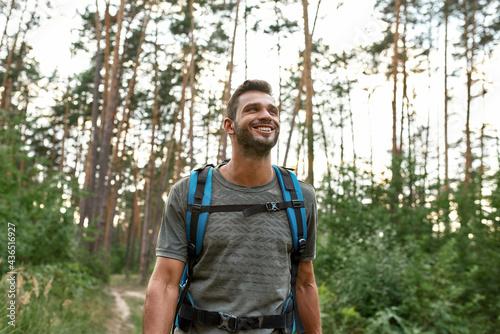 Fotografiet Portrait of smiling young caucasian man trekking in forest