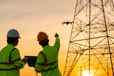 Engineers location help Technician use drone to fly inspections at the electric power station to view the planning work by producing electricity high voltage electric transmission tower at sunset