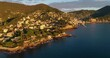 A village on the coast of the French Riviera under the sunset. We can see the houses in the mountain near the Mediterranean sea - aerial view 4K