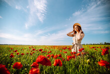 Young Woman Walking In Amazing Poppy Field. Summertime. Beautiful Woman Posing In The Blooming Poppy Field. Nature, Vacation, Relax And Lifestyle.