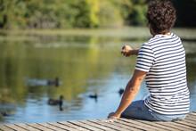 Handsome Dark-haired Man Feeding Ducks