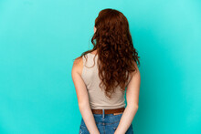 Teenager Reddish Woman Isolated On Blue Background In Back Position And Looking Back