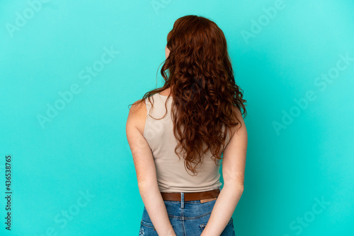 Fototapeta Teenager reddish woman isolated on blue background in back position and looking