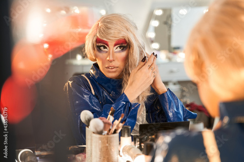 Drag queen with bright makeup preparing hi look while sitting at the dressing ta Fototapet
