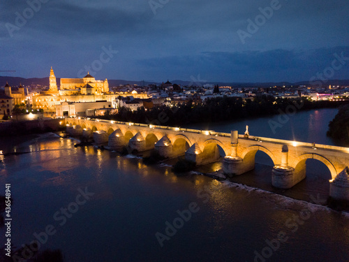 Obraz na plátně Scenic aerial view of lighted Roman bridge across Guadalquivir river and Mezquita-Catedral on background with Cordoba cityscape at twilight, Spain