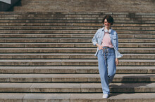 Young Confident Happy Student Smiling Pedestrian Woman 20s In Casual Jeans Clothes Eyeglasses Headphones Strolling Walk Go Down Conctrete Steps Outdoors People Youth Active Urban Lifestyle Concept