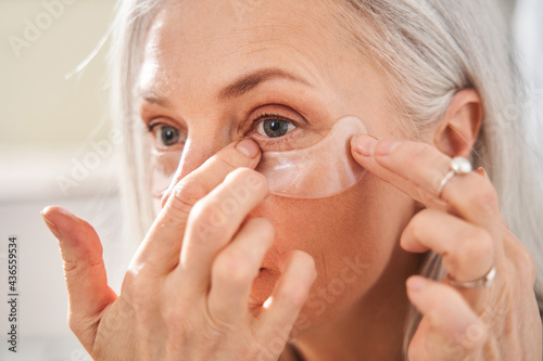Fotografiet Female is looking into the mirror while wearing eye patches against wrinkles