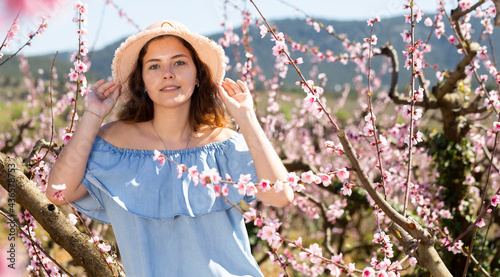 Fotografia Lovely female in blue dress and straw hat walking in blooming park, springtime c