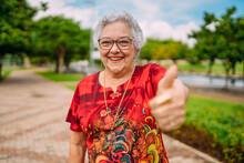 Joyful Senior Lady In Glasses Laughing Up Thumb. Latin American Woman. Brazilian Elderly Woman.