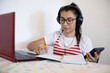 Woman wearing headphones, using laptop, using cell phone, writing notes and smiling, online class concept, teaching online