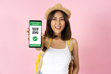 Happy Young Female Traveler Using Mobile Phone App Showing Travel Pass Of Covid-19 Vaccination Over Pink Isolated Background. Corona Virus Vaccinated Person For Travel Safety Concept