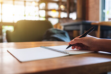 Closeup Image Of A Woman Writing On A Blank Notebook On The Table