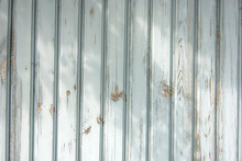 Flaky Paint On A Old Weathered Wooden Fence. Vintage Wood Background Wall. Peeling Paint Flakes. Old Weathered Wooden Plank Painted In Blue Color. Texture Of Old Wooden Boards With Peeling Paint.