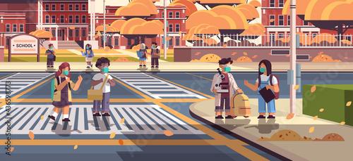 Fotografija mix race schoolchildren in masks crossing road on crosswalk pupils walking to sc