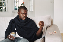 Mid Adult Man Sitting On Sofa At Home