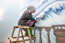 Mature Woman Artist Draws A Mural On A Marine Theme Sitting On A Ladder