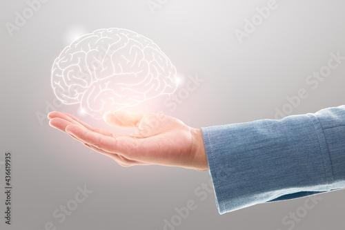 Photo Female doctor holding brain illustration against the gray background