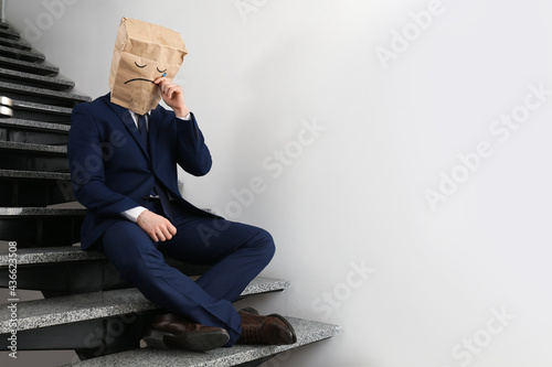 Canvas Print Man wearing paper bag with drawn sad face indoors. Space for text